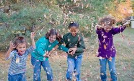 Muchachas que juegan en hojas foto de archivo