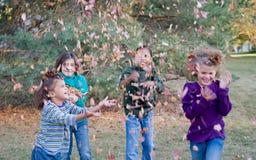 Muchachas que juegan en hojas fotos de archivo libres de regalías