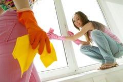 Muchachas que lavan la ventana Imágenes de archivo libres de regalías