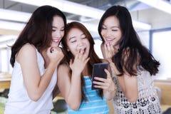 Muchachas que leen el mensaje y que ríen junto Imagen de archivo