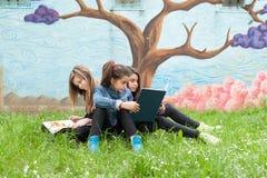 Muchachas que leen un libro en el parque Imágenes de archivo libres de regalías