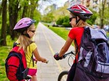 Muchachas que llevan el casco de la bicicleta y el ciclyng de la mochila Fotografía de archivo libre de regalías