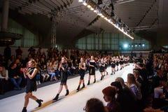 Muchachas que llevan los vestidos negros que van a lo largo del podio fotos de archivo