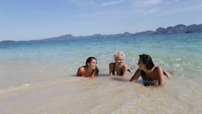 Muchachas que mienten en agua en la playa que habla, comunicación de risa de los turistas de la mujer joven almacen de metraje de vídeo