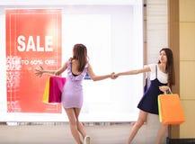 Muchachas que miran el cartel del descuento y que hacen compras en la alameda imagenes de archivo