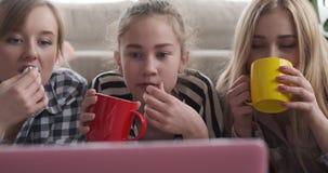 Muchachas que miran el contenido de los medios en el ordenador portátil mientras que comiendo café y palomitas almacen de video