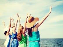 Muchachas que miran el mar con las manos para arriba Fotografía de archivo libre de regalías