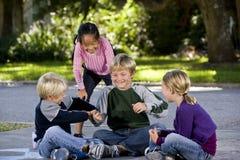 Muchachas que miran jugar de los muchachos Imagen de archivo libre de regalías