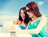 Muchachas que miran la PC de la tableta en café Foto de archivo libre de regalías