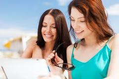 Muchachas que miran la PC de la tableta en café Imágenes de archivo libres de regalías