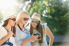 Muchachas que miran las fotos en su cámara las vacaciones de verano fotos de archivo