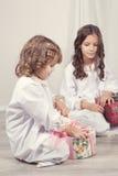 Muchachas que miran los regalos de la Navidad Imagenes de archivo