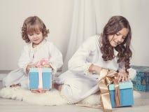Muchachas que miran los regalos de la Navidad Fotos de archivo libres de regalías