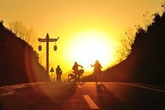 Muchachas que montan la bicicleta en la puesta del sol Imagen de archivo libre de regalías