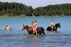 Muchachas que nadan a caballo en el lago Fotografía de archivo libre de regalías