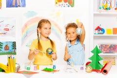Muchachas que pintan las bolas del Año Nuevo para el árbol de navidad Foto de archivo