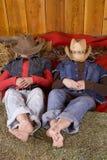 Muchachas que ponen con los sombreros sobre pies de las pistas en el heno Fotografía de archivo