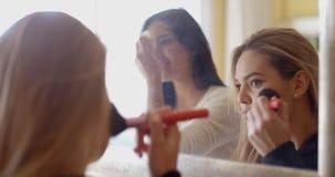 Muchachas que ponen maquillaje delante de un espejo almacen de metraje de vídeo