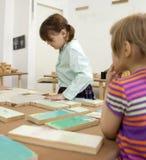 Muchachas que recogen rompecabezas de madera Imagenes de archivo