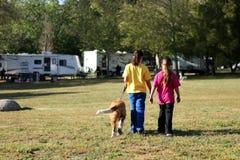 Muchachas que recorren un perro mientras que acampa Imágenes de archivo libres de regalías