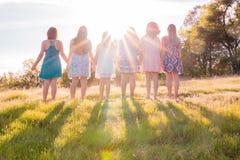 Muchachas que se colocan junto que hacen frente a la puesta del sol brillante Imagen de archivo libre de regalías