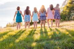 Muchachas que se colocan junto que hacen frente a la puesta del sol brillante Fotografía de archivo libre de regalías