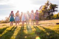 Muchachas que se colocan junto que hacen frente a la puesta del sol brillante Foto de archivo