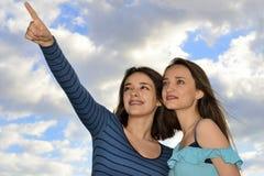 Muchachas que se colocan sobre el cielo azul y señalar Imagen de archivo libre de regalías