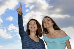 Muchachas que se colocan sobre el cielo azul y señalar Imagen de archivo
