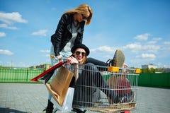Muchachas que se divierten con el carro de la compra Foto de archivo libre de regalías
