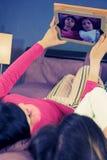 Muchachas que se divierten que toma imágenes con la tableta en cama Imágenes de archivo libres de regalías