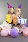 Muchachas que se sientan con los regalos y los globos coloridos Fotografía de archivo