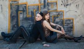 Muchachas que se sientan delante de la pared de la pintada Foto de archivo