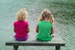 2 muchachas que se sientan en el banco Imagen de archivo