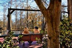 Muchachas que se sientan en el banco en el parque Imágenes de archivo libres de regalías