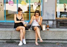Muchachas que se sientan en el bocado del banco en suizo Riviera de Montreux Fotografía de archivo