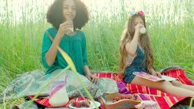 Muchachas que se sientan en el campo y la leche de consumo metrajes
