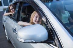 Muchachas que se sientan en el coche cerca de la ventana Imágenes de archivo libres de regalías