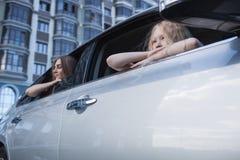 Muchachas que se sientan en el coche cerca de la ventana Fotos de archivo libres de regalías