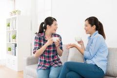 Muchachas que se sientan en el sofá de la sala de estar que habla junto Fotografía de archivo libre de regalías