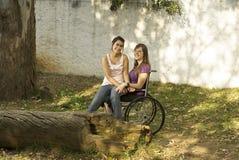Muchachas que se sientan en sillón de ruedas Imagenes de archivo