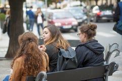 3 muchachas que se sientan en un banco Foto de archivo