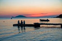 Muchachas que se sientan en un embarcadero en la puesta del sol en Sithonia Fotos de archivo
