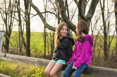 Muchachas que sientan hablar de la cerca Fotos de archivo libres de regalías