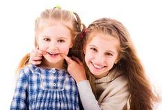 Muchachas que sonríen y que se relajan junto aislado en el fondo blanco Foto de archivo libre de regalías