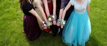 Muchachas que sostienen los brazos hacia fuera con las flores del ramillete para el baile de fin de curso foto de archivo