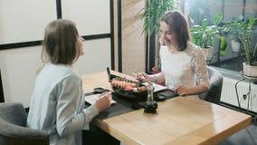 Muchachas que susurran confering privado en restaurante almacen de video