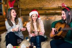 Muchachas que tienen una fiesta de Navidad casera foto de archivo