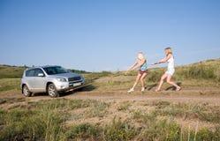 Muchachas que tiran del coche Foto de archivo libre de regalías
