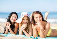 Muchachas que toman el sol en la playa Foto de archivo